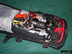 Close-up of the inside of the main pocket of the pack with camera, windbreaker, Gatorade, and two-way radio visible.