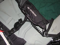 Photo of the shoulder strap and waist belt on the pack, with a radio speaker-mic on the chest strap.
